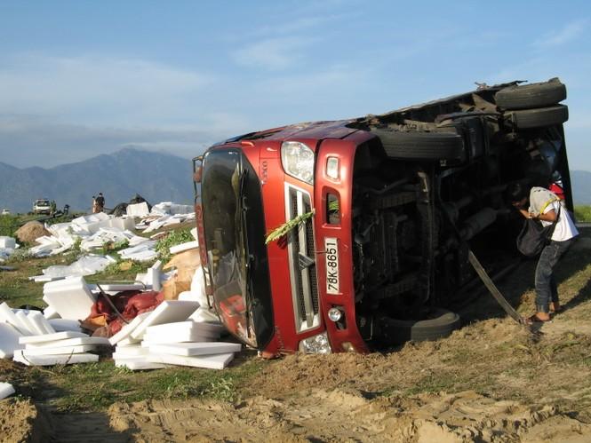Xe tải 78K-8651 bị lật nghiêng bên vệ đường, hàng hóa văng tung tóe.