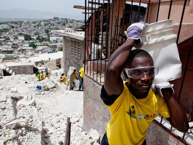 Một người dân ở thủ đô Port-au- Prince đi nhặt nhạnh những gì còn sót lại trong một ngôi nhà đổ nát. Chiếc áo anh mặc, giống như của nhiều người khác, là hàng viện trợ của chính phủ Mỹ. Ảnh: Getty Images