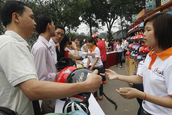 Điểm đổi mũ bảo hiểm trợ giá tại trước cổng công viên Thống Nhất, Hà Nội