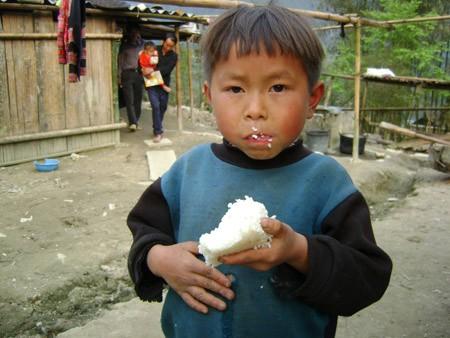 Đứa con thứ 9 của vợ chồng bà Sú hồn nhiên cầm cục cơm trắng ăn ngon lành