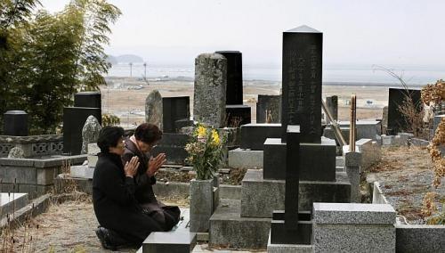 Hai người phụ nữ Nhật Bản có mặt tại nghĩa trang Rikuzentakata, tỉnh Iwate để cầu nguyện cho người nhà đã thiệt mạng trong thảm họa động đất năm 2011