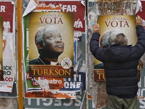 Một người tìm cách gỡ bỏ apphich ủng hộ Đức hồng y Peter Turkson của Ghana làm giáo hoàng tại Rome (ảnh chụp ngày 1-3)