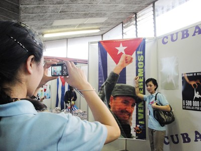 Chụp hình cho nhau bên ảnh Chủ tịch Fidel