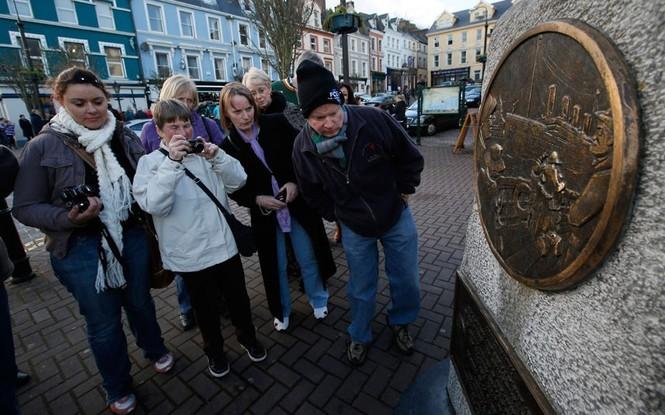 Hành khách đã có mặt ở bến cảng Cobh, Ireland vào hôm nay 10-4. Trong ảnh các hành khách đang đứng trước đài tưởng niệm được xây dựng tại đây.