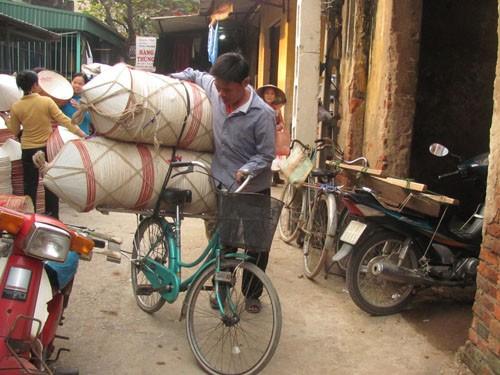 Anh Tuấn (xã Phương Trung, huyện Thanh Oai, Hà Nội) đang đưa số nón đã mua được về nhà. Sau đó số nón này sẽ được phân phối đi nơi khác.