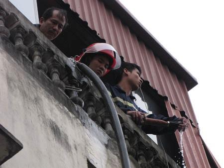 Một bộ phận phải mang vòi nước sang nhà bên cạnh, chữa cháy trên nóc ngôi nhà số 155 Nguyễn Thái Học