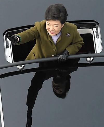 Tổng thống Hàn Quốc Park Geun-hye đứng trên chiếc limousine tươi cười vẫy tay chào người dân hôm 25/2