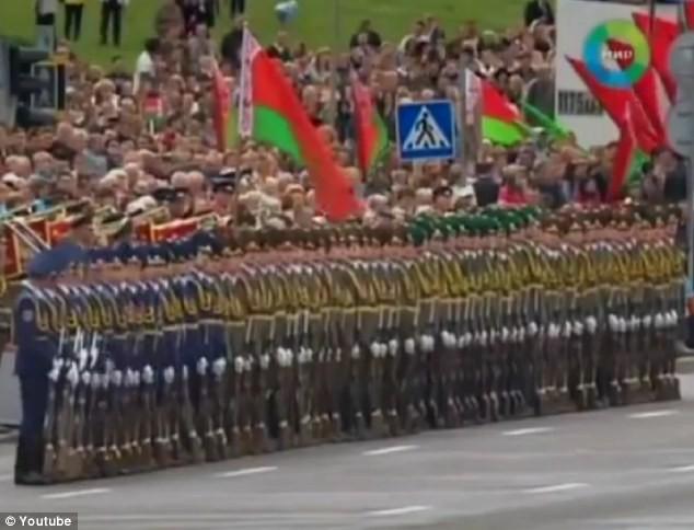 Lực lượng quân đội Belarus đứng xếp hàng, tay cầm súng và biểu diễn theo hiệu ứng Domino