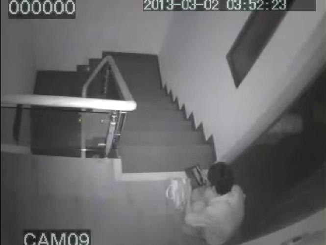 Hình ảnh được camera quay lại tên trộm đang ngồi đếm tiền trong hành lang căn nhà