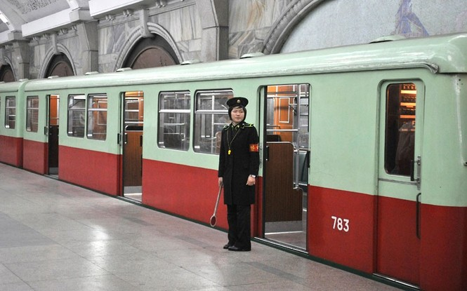"""""""Quy tắc của một nhiếp ảnh gia là chụp ảnh trước và hỏi sau. Song lực lượng bảo vệ tại Triều Tiên lại tỏ ra không mấy thân thiện. Khi ở khách sạn, chúng tôi được yêu cầu không ra ngoài nếu không có hướng dẫn viên du lịch đi cùng. Chúng tôi đã thử làm trái quy định 3 lần nhưng không đi quá được 3 km đã phải quay về"""", ông Bergman chia sẻ.             Trong ảnh là một nữ nhân viên điều hành làm việc tại Trạm tàu điện ngầm Bình Nhưỡng"""
