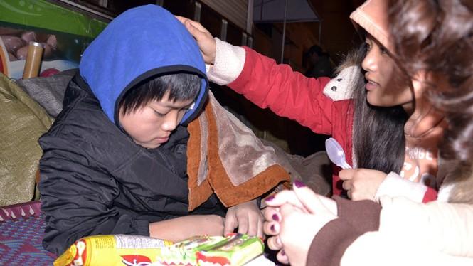 3g sáng, bé Nguyễn Anh Tuấn - 13 tuổi - co ro trong chiếc chăn mỏng, không ngủ được vì trời lạnh. Được nhận quà, em tủi thân chực khóc... - Ảnh: HUỆ BẠCH