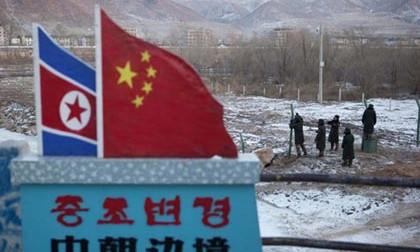 Các cảnh sát bán quân sự Trung Quốc đang xây hàng rào gần cột mốc biên giới cắm quốc kỳ Triều Tiên và Trung Quốc ở thị trấn Tumen, tỉnh Jilin, Trung Quốc