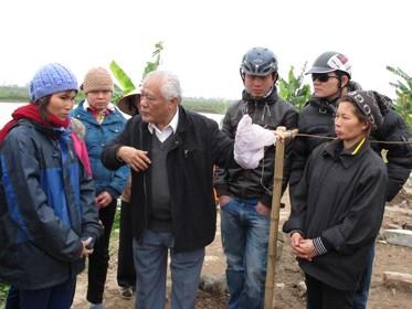Phó chủ tịch Hội Nghề cá Việt Nam Võ Văn Trác (thứ ba từ trái qua) thăm hỏi vợ con ông Quý, ông Vươn ngay trên nền đất của căn nhà hai tầng đã bị phá hủy. Ảnh: Thân Hoàng
