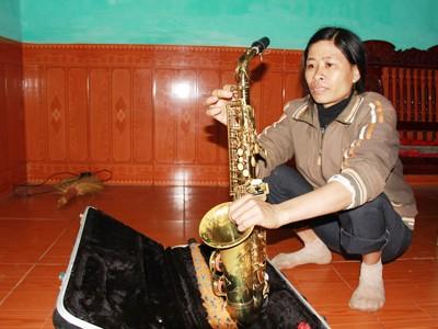 Chị Bùi Thị Nhàn lau chùi, bảo dưỡng cây saxophone của mình, chuẩn bị đi phục vụ đám hiếu gần nhà. Ảnh: Trường Phong