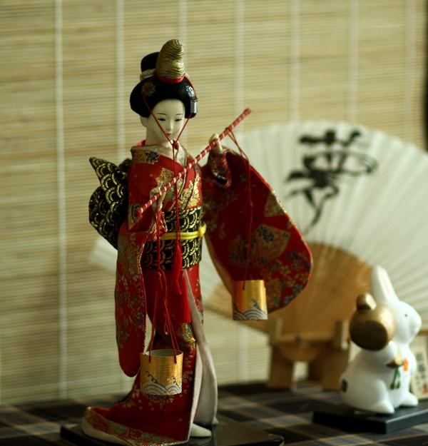 Cùng với Daruma còn có những búp bê khác được trưng bày: Kimono bằng sứ, bên ngoài là lớp áo bằng vải và giấy bồi