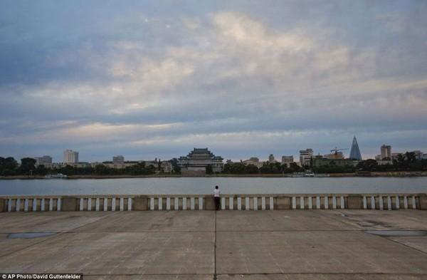 1 phụ nữ đang đứng bên bờ sông Taedong nhìn về phía thủ đô Bình Nhưỡng