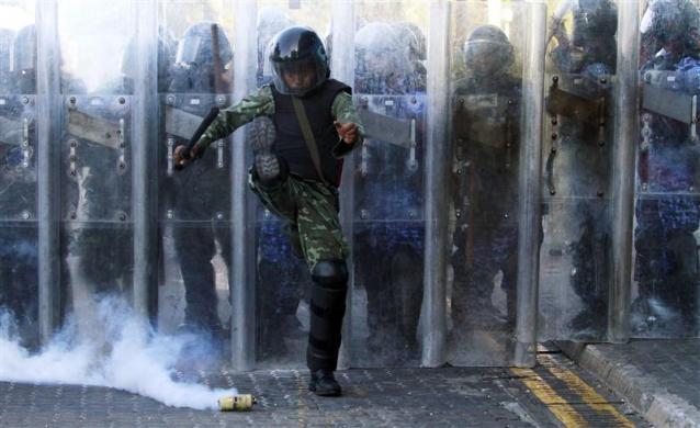 Tổng thống Maldivian Mohamed Nasheed đang chịu áp lực yêu cầu từ chức của người dân. Bức ảnh cho thấy một viên cảnh sát chống bạo động đang cố nhảy ra khỏi một quả lựu đạn do nhóm biểu tình thực hiện ở bên ngoài trụ sở tổng thống Maldivian làm việc. Ảnh: Reuters