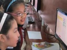 Các em học sinh trường tiểu học Bế Văn Đàn (Thanh Khê, Đà Nẵng) đang chơi máy tính khi kỹ sư phần mềm của Google đến thăm quan.