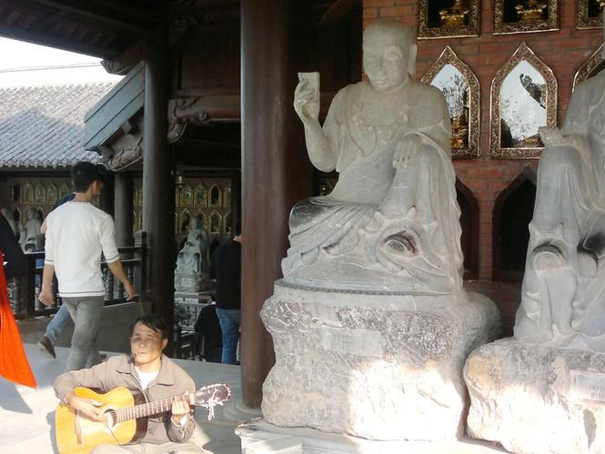 Người đàn ông mù lòa chơi bản đàn buồn bã và hát những lời ai oán về đời mình ngay cạnh những bức tượng La Hán (chụp tại chùa Bái Đính mới)