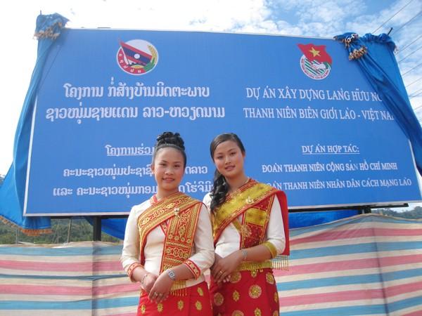 Hai thiếu nữ Lào bên tấm biển Dự án Làng Thanh niên Hữu nghị Biên giới Lào - Việt vừa được hai Bí thư thứ nhất cắm ở tỉnh Bolikhamxay