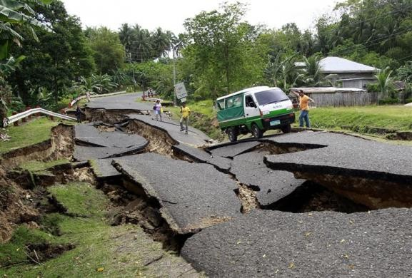 Đoạn đường tại La Libertad, Negro, miền trung Philippines bị hư hỏng nặng sau khi một trận động đất xảy ra ngày 7-2. Một số xe cứu thương đang phải di chuyển nạn nhân tới bệnh viện. Ảnh: Reuters