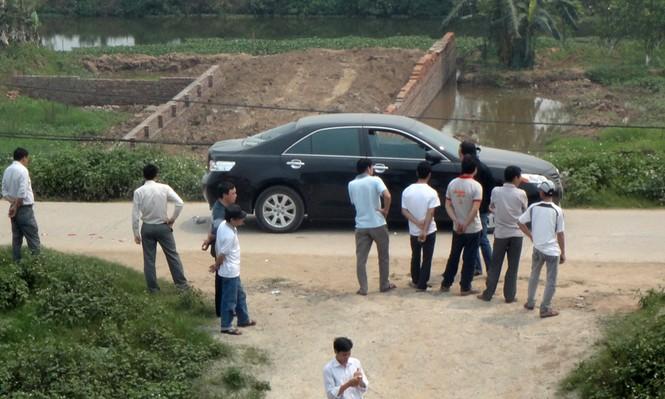 Người dân địa phương bên một chiếc xe bỏ lại hiện trường