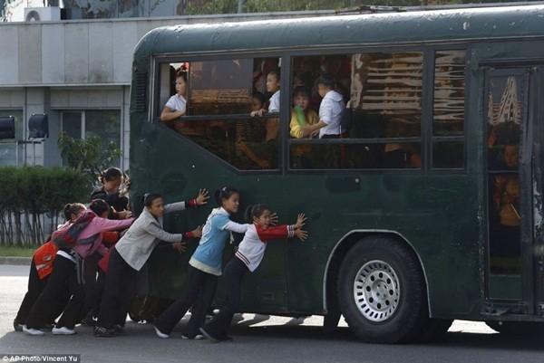 Học sinh đang giúp đẩy chiếc xe bus tại thủ đô Bình Nhưỡng