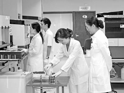 PGS.TS Bạch Khánh Hòa (bìa phải) làm việc cùng các đồng nghiệp tại Viện Huyết học & Truyền máu T.Ư.             (Ảnh do nhân vật cung cấp)