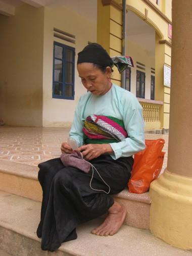 Bà Mu ngồi bên ngoài lớp học chờ các cháu học xong. Ảnh: Hoàng Phương