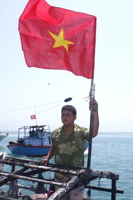 Bùi Văn Phái bên lá cờ tổ quốc mới
