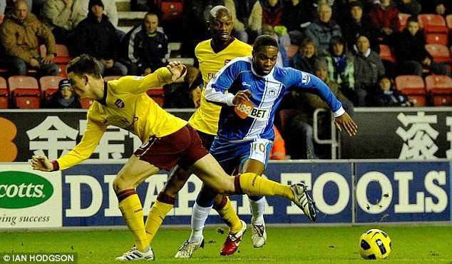 Dẫn trước và được chơi hơn người nhưng Arsenal (áo vàng) vẫn bị Wigan cầm hòa