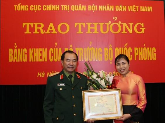 Trung tướng Mai Quang Phấn, Phó Chủ nhiệm Tổng cục Chính trị, Quân đội Nhân dân Việt Nam trao bằng khen cho họa sỹ Nguyễn Thị Thu Thủy