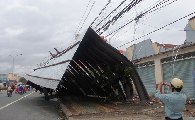 Toàn bộ mái nhà của dãy ki ốt thuộc công ty Xổ số Bình Dương nằm trên Đại Lộ Bình Dương (phường Hiệp Thành) bị hất tung ra đường, đè lên dây điện