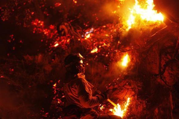 Một lính cứu hỏa đang cố gắng dập tắt đám cháy tại núi vùng Jubrique, gần Malaga, miền nam Tây Ban Nha. Ảnh: Reuters