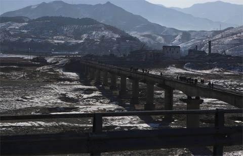 Người dân đi trên một cây cầu đường sắt bắc qua sông ở phía nam núi Myohyang và phía bắc thủ đô Bình Nhưỡng ngày 23/2