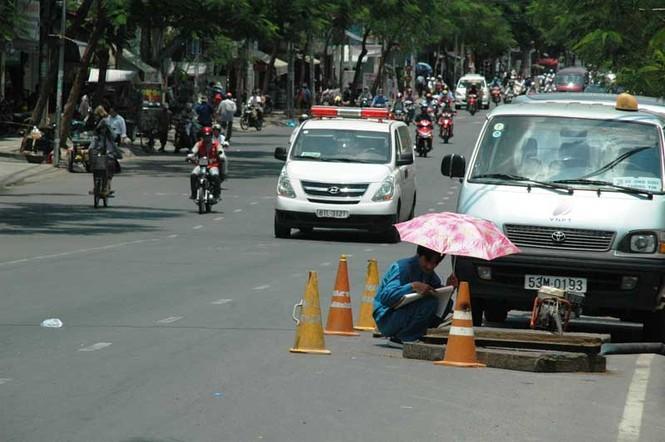 Người công nhân sửa cống phải mượn nhà dân gần đó một chiếc dù để tránh nóng trong khi làm việc