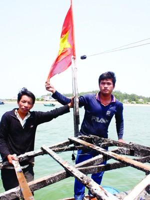Anh Thạnh và anh Phải bên lá cờ Tổ quốc. Ảnh: Nguyễn Thành