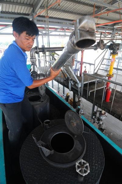 Nạp nhiên liệu vào xe bồn tại tổng kho xăng dầu Nhà Bè, TP.HCM. Doanh nghiệp đầu mối chỉ bảo đảm chất lượng xăng dầu đối với các cửa hàng trực thuộc, còn các đại lý thì... chịu! - Ảnh: Tuổi Trẻ
