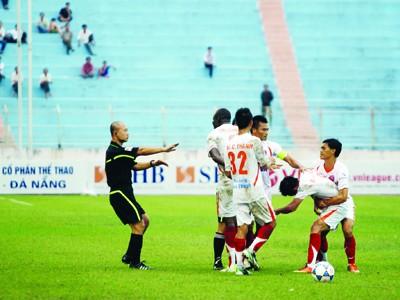 Các cầu thủ XMXT Sài Gòn ngăn cản Việt Cường xông tới trọng tài Nguyễn Văn Kiên. Ảnh: Hà Ngọc