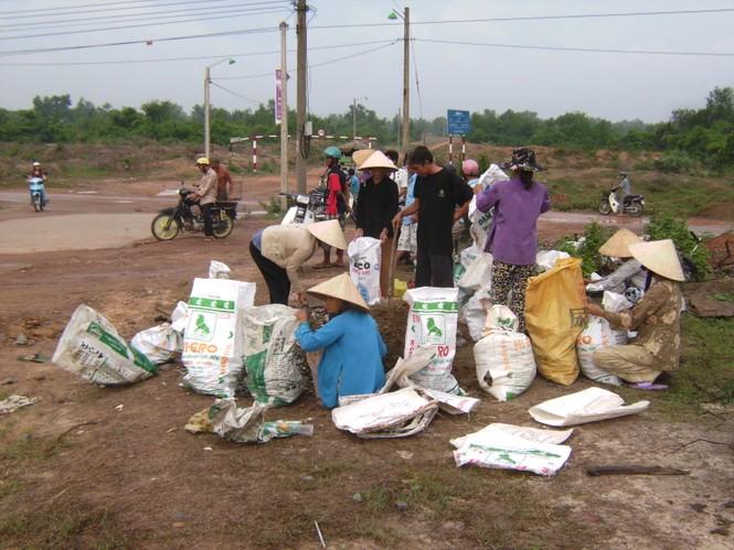 Người dân xã Tam An mang đất đá đến lấp cống xả thải