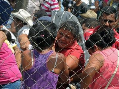 Những người thân của tù nhân đứng trước cổng nhà tù tại Comayagua, Honduras