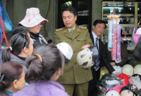Ông Trần Hùng, Phó Cục trưởng Cục Quản lý thị trường trực tiếp giải thích cho người dân về mũ bảo hiểm không đạt chất lượng. Ảnh: V.S