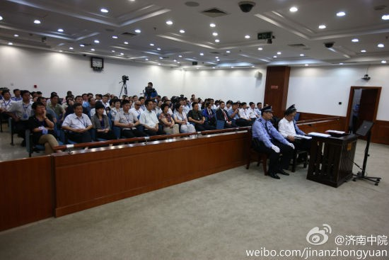 Ông Bạc Hy Lai mặc áo sơ mi trắng, quần đen được hai cảnh sát