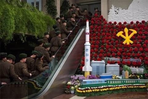 Binh sĩ Triều Tiên đi cầu thang di động qua một mô hình Tên lửa Unha khi họ tới một triển lãm ở Bình Nhưỡng ngày 17/2