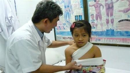 Bác sĩ Lĩnh đang băng cố định xương cho bé Anh - Ảnh: Vietnamnet.vn.