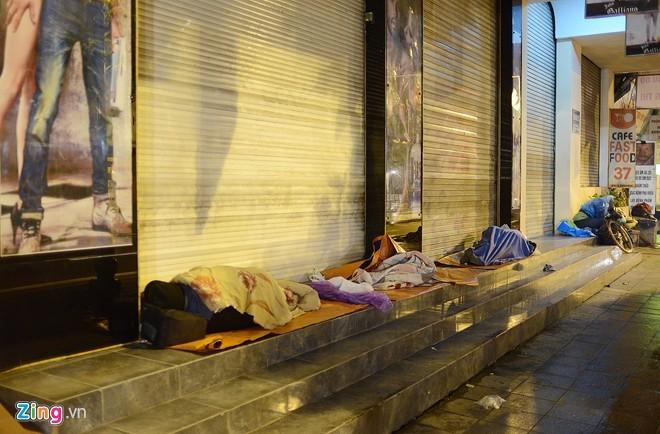 Người vô gia cư mặc áo mưa ngủ vỉa hè trong đêm giá - ảnh 2
