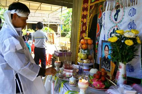 Con trai bà Tri bên bàn thờ mẹ. Ảnh: Nguyễn Dương