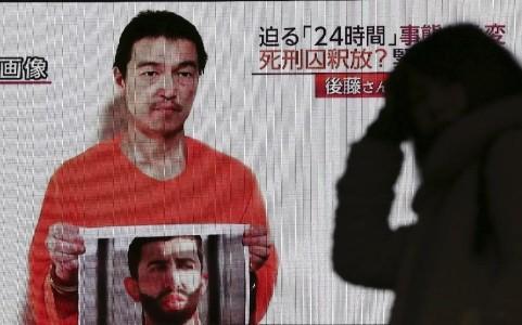 Một người Nhật Bản theo dõi thông tin về con tin Goto (Ảnh Reuters)